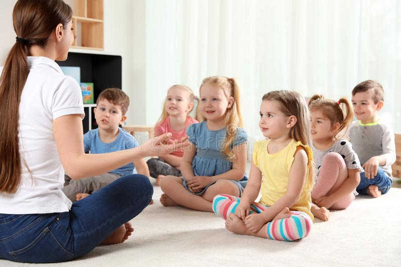 Kindergarten teacher and little children. Learning and playing royalty free stock images
