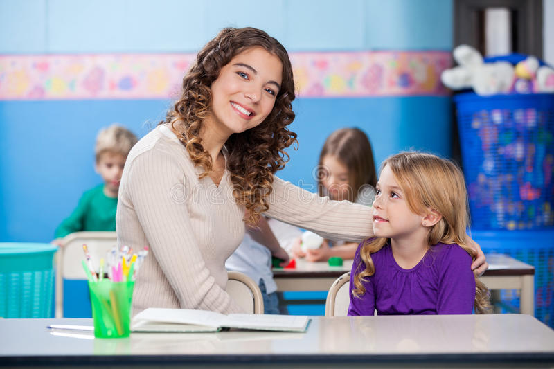 Kindergarten Teacher With Little Girl In Classroom royalty free stock photography