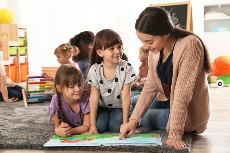 Kindergarten teacher reading book with cute girls while other children playing together stock photos