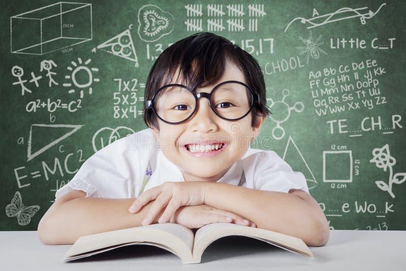 Kindergartenschüler mit dem Buchlächeln stockbild