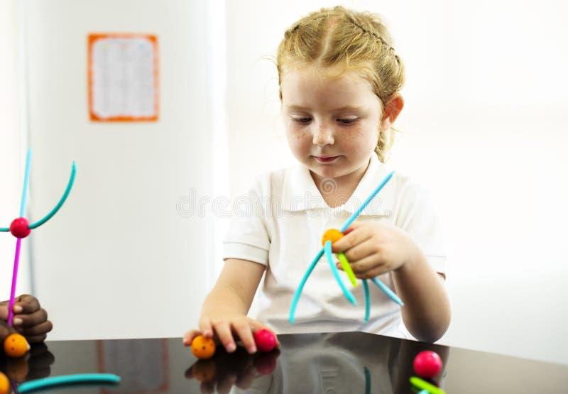Kindergartenstudent, der das Lernen von Strukturen von den Spielwaren hält stockbild