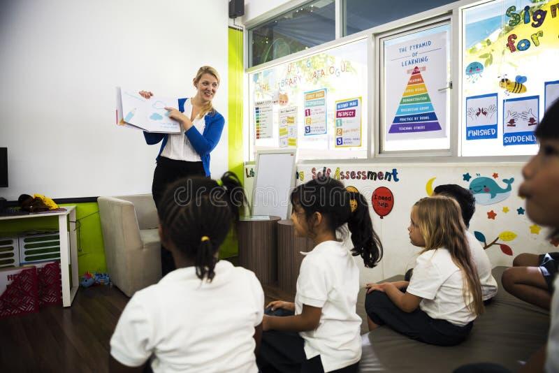 Kindergartenstudenten, die auf dem Boden im Klassenzimmer sitzen lizenzfreie stockfotos