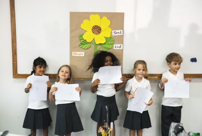 Kindergartenstudenten, die darstellend stehen lizenzfreie stockfotos