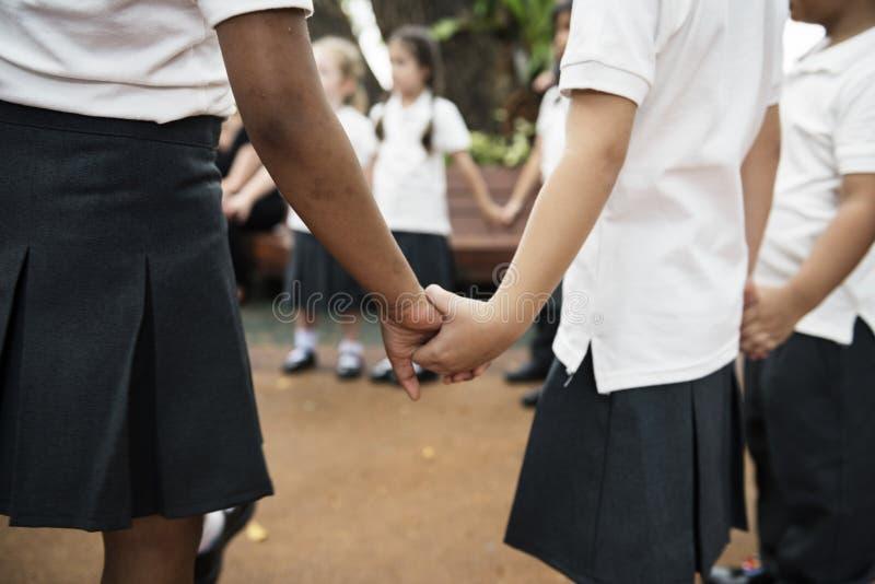 Kindergartenstudenten, die Händchenhalten stehen lizenzfreies stockfoto