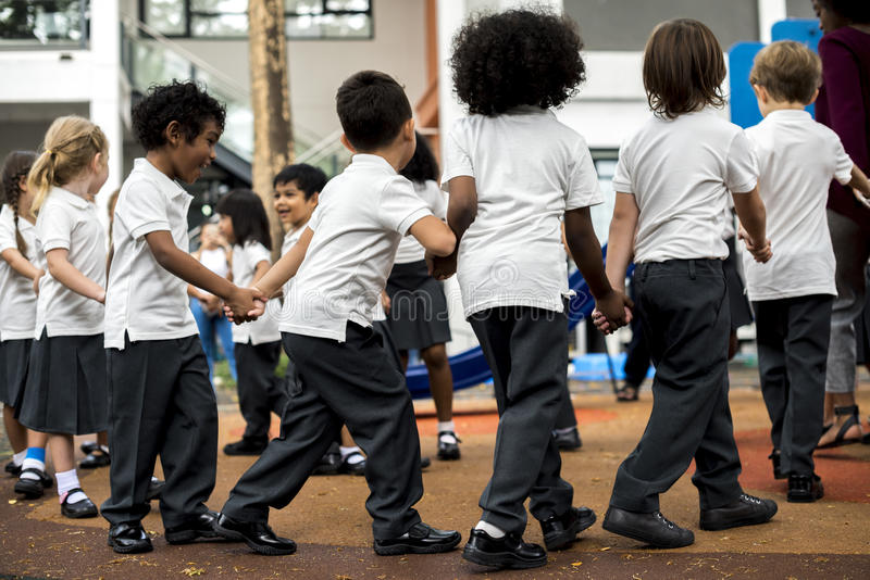 Kindergartenstudenten, die Händchenhalten stehen stockbilder