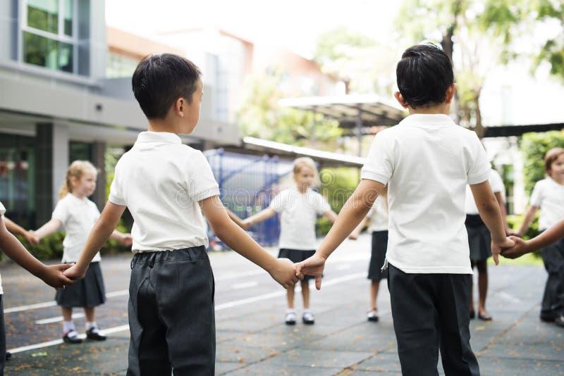 Kindergartenstudenten, die Händchenhalten zu stehen lizenzfreie stockfotografie