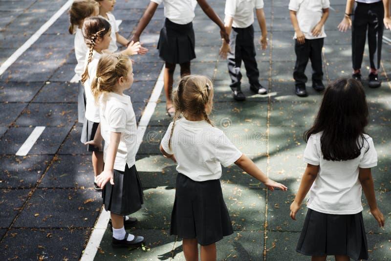 Kindergartenstudenten, die Händchenhalten zu stehen lizenzfreies stockbild