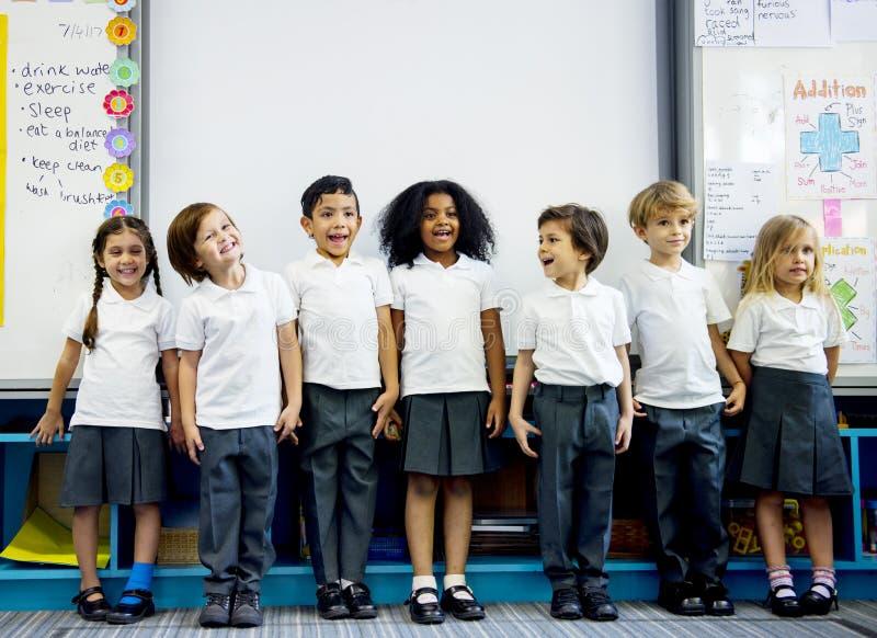 Kindergartenstudenten, die zusammen in den clas stehen lizenzfreies stockbild