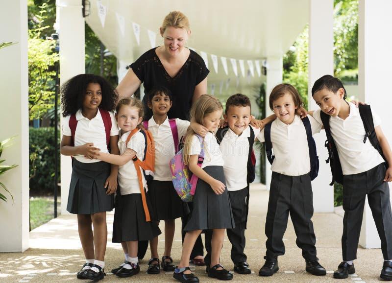 Kindergartenstudenten, die zusammen in der Schule stehen lizenzfreies stockfoto