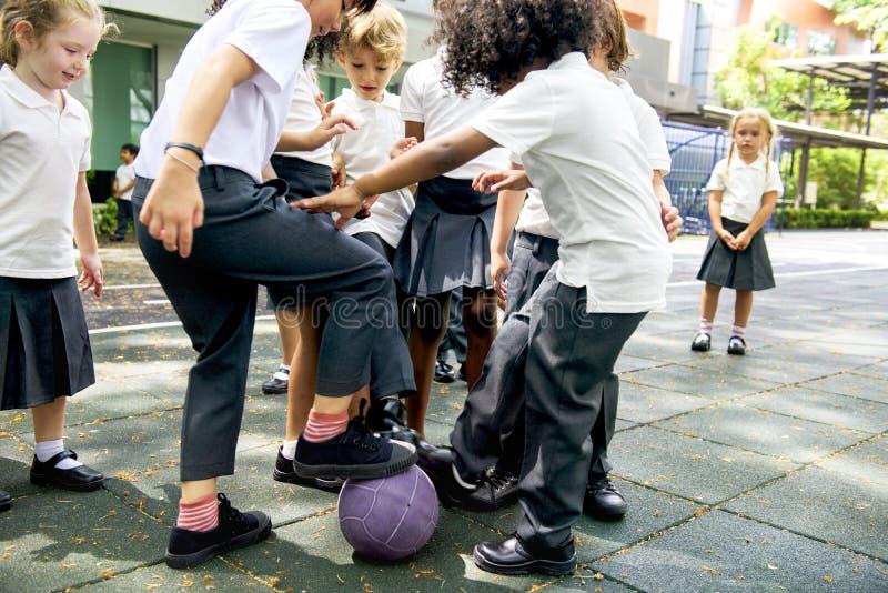 Kindergartenstudenten, die zusammen Fußball spielen stockfotografie