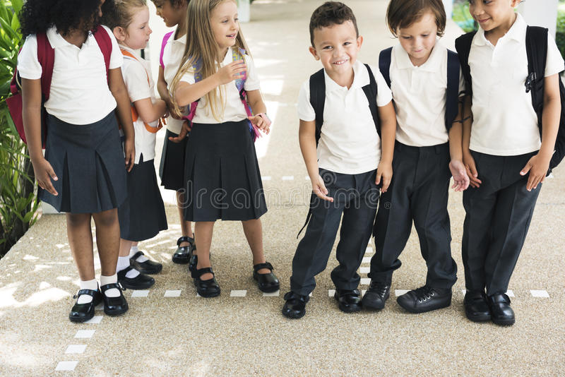 Kindergartenstudenten, die zusammen im scho stehen lizenzfreies stockfoto