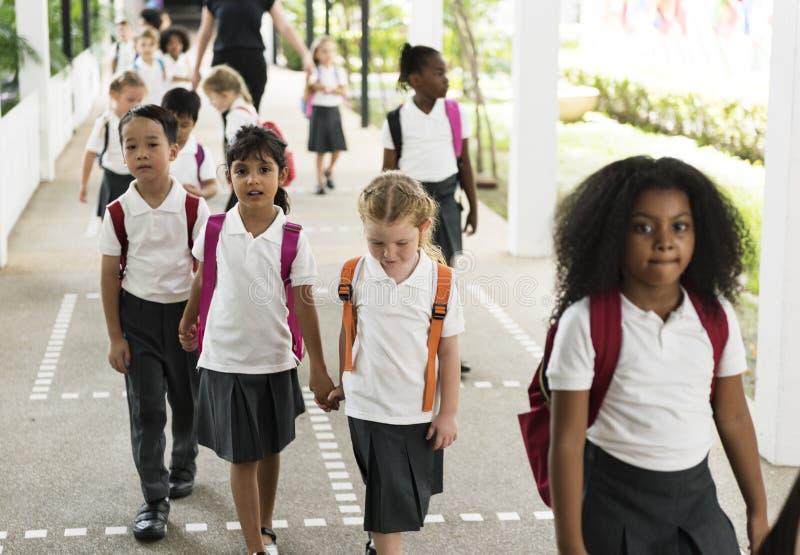 Kindergartenstudenten, die zusammen in Schule gehen stockfoto