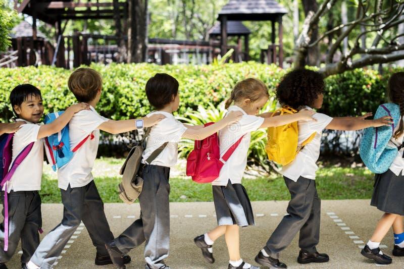 Kindergartenstudenten, die zusammen in Schule gehen lizenzfreies stockbild