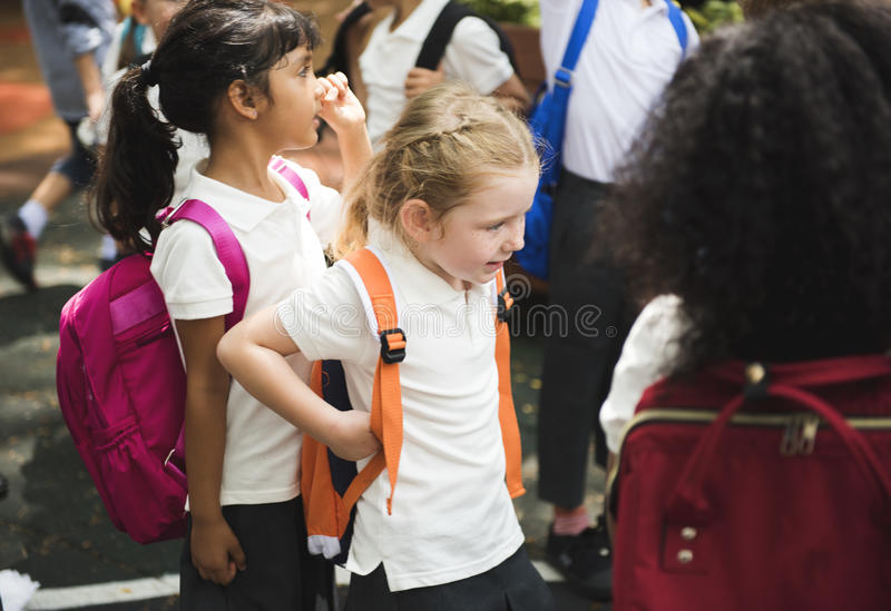 Kindergartenstudenten mit dem Rucksack, der zusammen steht stockfotos