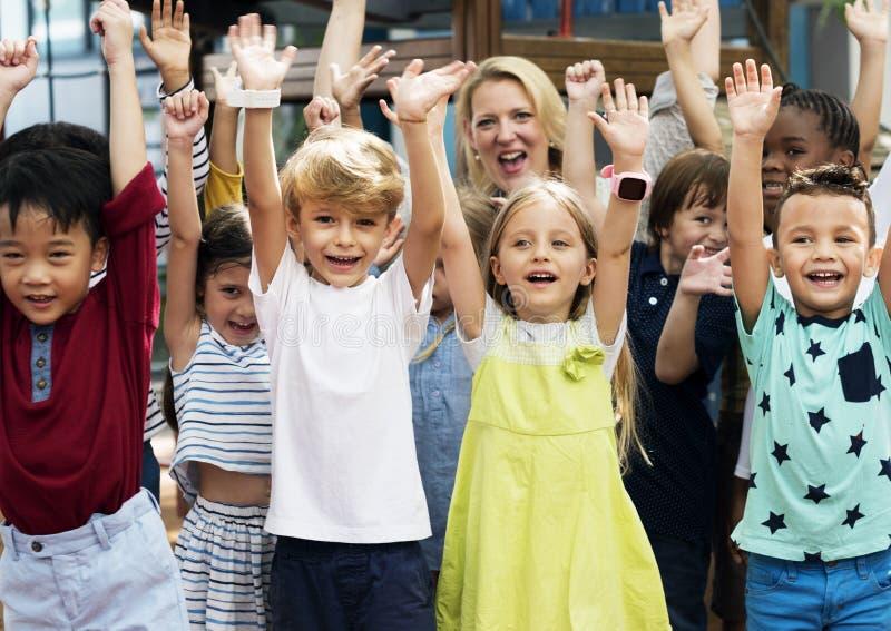 Kindergartenstudenten mit den Armen angehoben lizenzfreie stockfotos