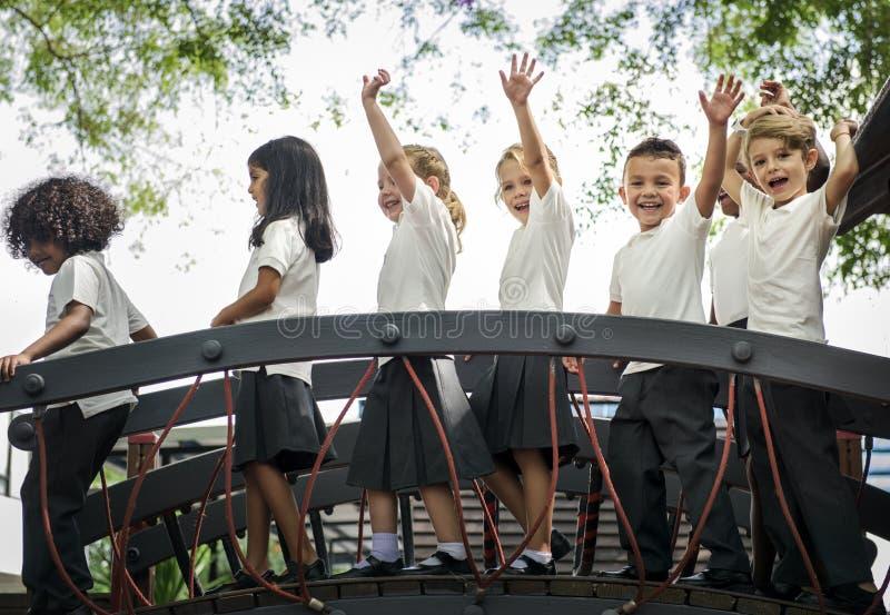 Kindergartenstudenten mit den Armen angehoben stockfotografie