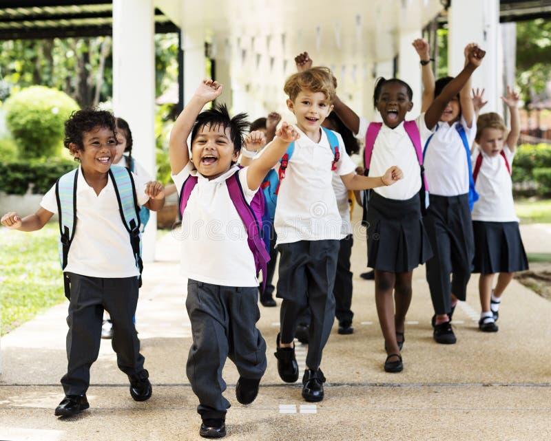Kindergartenstudentenlaufen nett nach Klasse stockbilder