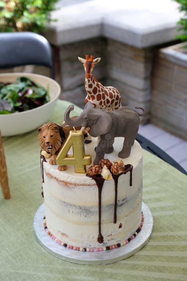 Kindergeburtstagskuchen mit den afrikanischen Tieren des Spielzeugs, die mit genieselter Schokoladensoße auf weißem icingwit über stockbild