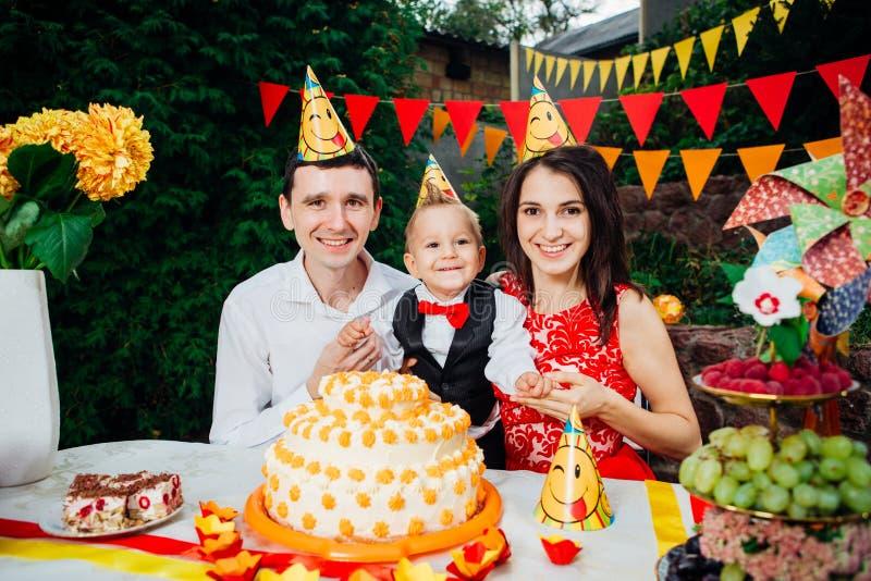 Kindergeburtstagsthema kaukasische Leute der dreiköpfigen Familie, die im Hinterhof des Hauses an einem festlichen verzierten Tis stockfoto