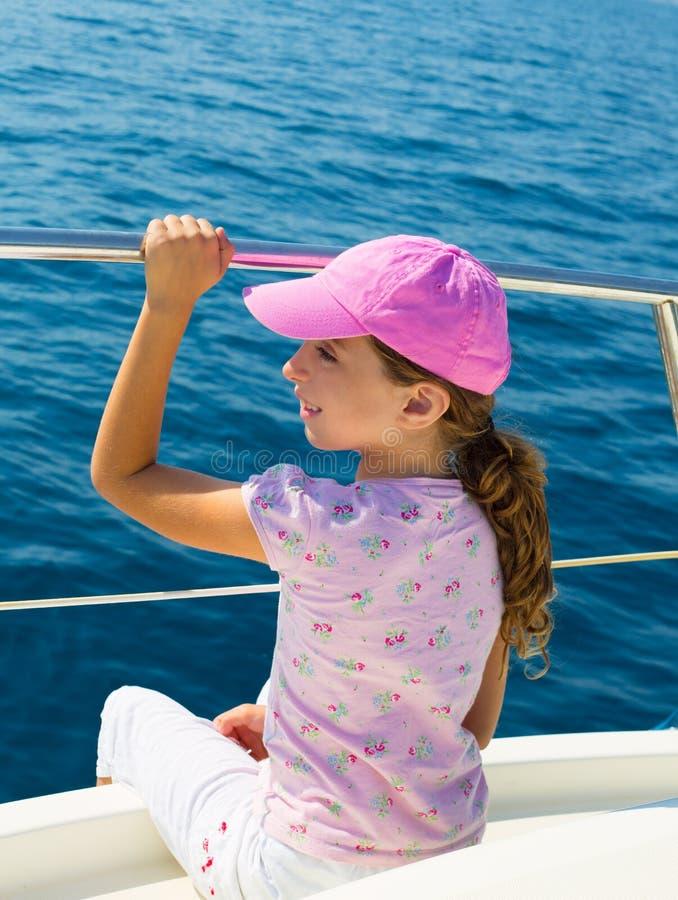 Kinderglückliches Mädchen, das glückliches Boot mit Schutzkappe segelt lizenzfreie stockbilder