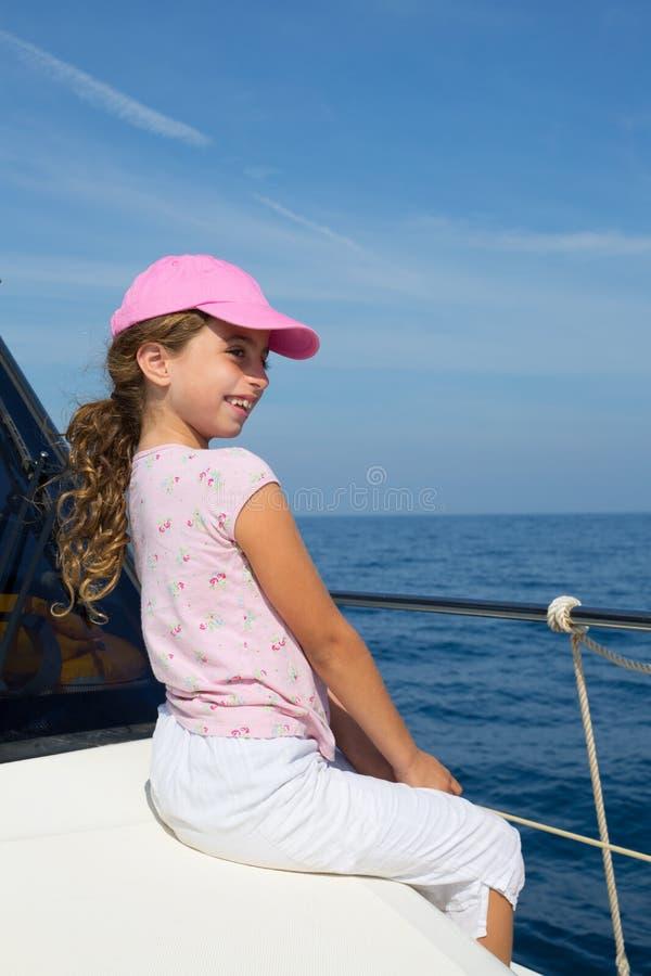Kinderglückliches Mädchen, das glückliches Boot mit Schutzkappe segelt stockfoto