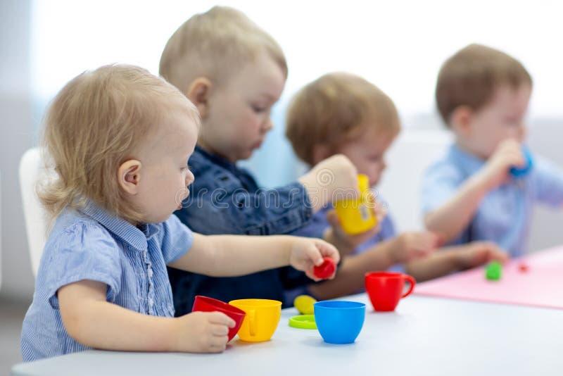 Kindergruppe, die K?nste und Handwerk im Spielzimmer mit Interesse lernt lizenzfreies stockfoto