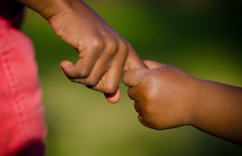 Kinderhändchenhalten im warmen Licht lizenzfreies stockbild