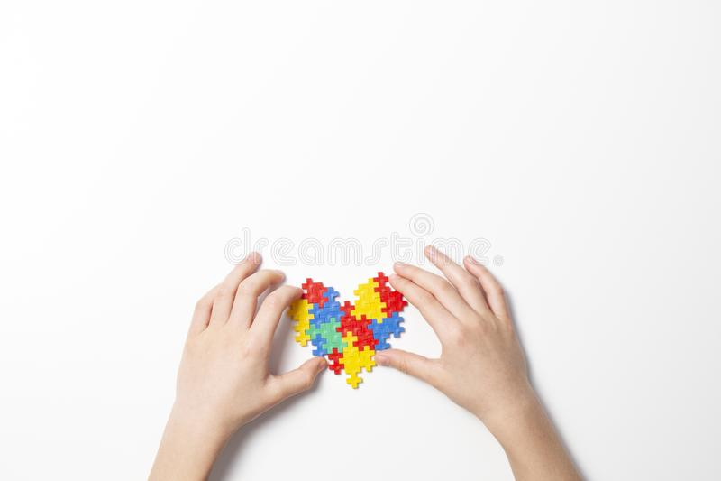 Kinderhände, die buntes Herz auf weißem Hintergrund halten Weltautismusbewusstseins-Tageskonzept stockfotos