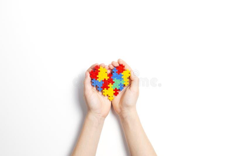 Kinderhände, die buntes Herz auf weißem Hintergrund halten Weltautismusbewusstseins-Tageskonzept stockbild