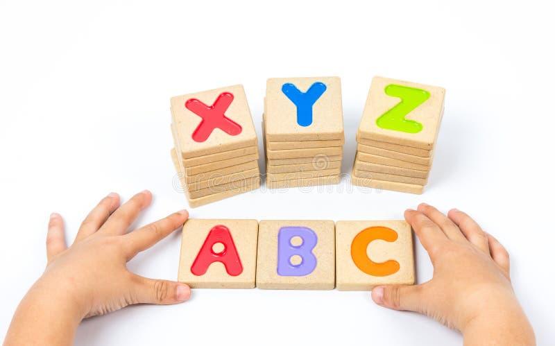 Kinderhände, die hölzernen Alphabetblock spielen lizenzfreies stockbild