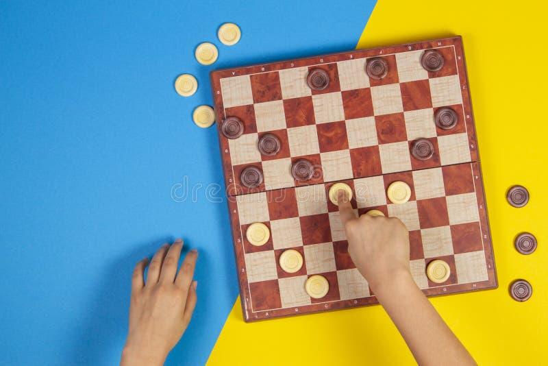 Kinderhände, die Kontrolleure auf KontrolleurBrettspiel über gelbem und blauem Hintergrund, Draufsicht spielen stockbilder