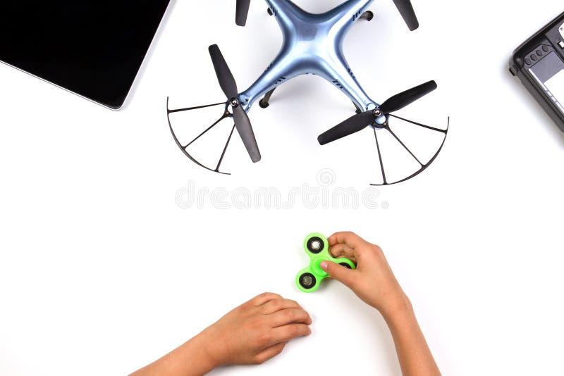 Kinderhände, die mit Unruhespinnerspielzeug spielen Drohne und Fernprüfer auf weißem Hintergrund stockbilder