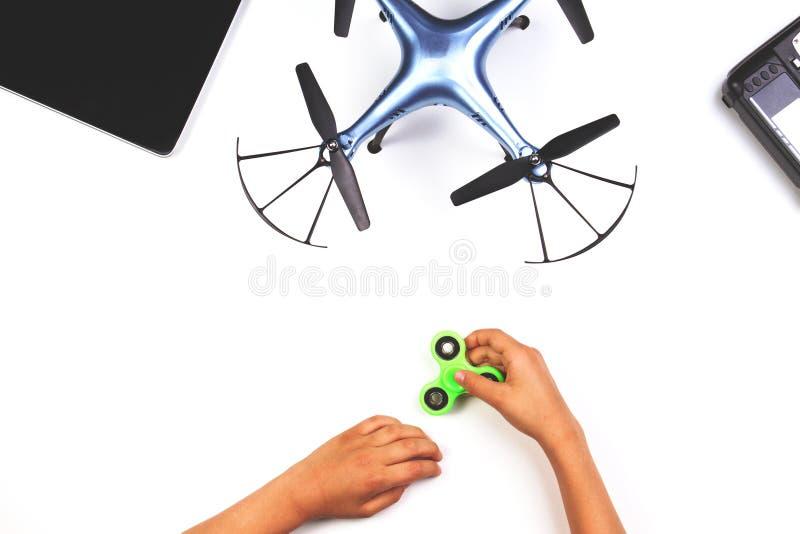 Kinderhände, die mit Unruhespinnerspielzeug spielen Drohne und Fernprüfer auf weißem Hintergrund stockbild
