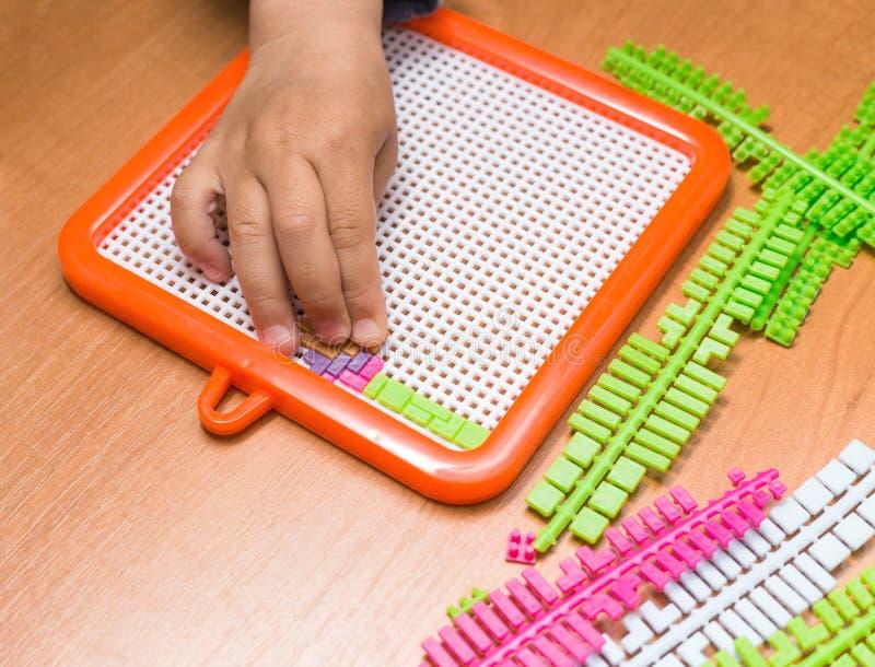Kinderhände, die Puzzlespiel zusammenbauen stockfotografie