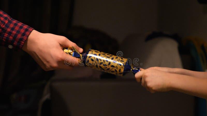 Kinderhände, die zu Hause Weihnachtscracker halten und ziehen lizenzfreies stockfoto