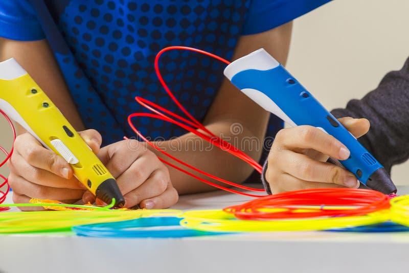 Kinderhände mit Stift des Drucken 3d und bunte Fäden auf weißer Tabelle stockfoto