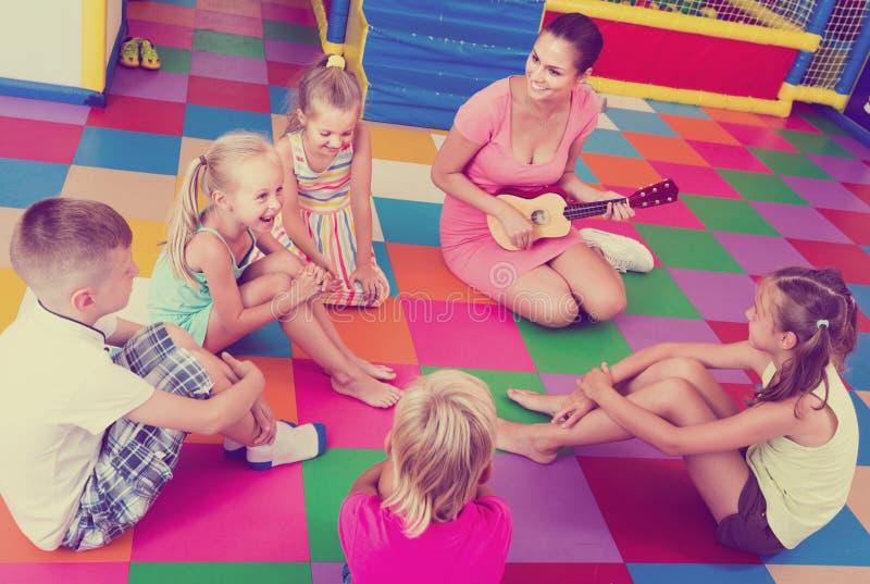 Kinderhörender Lehrer, der Musikerinstrument spielt stockfoto