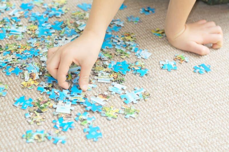 Kinderhand, die komplexes Puzzlespiel spielt stockbild