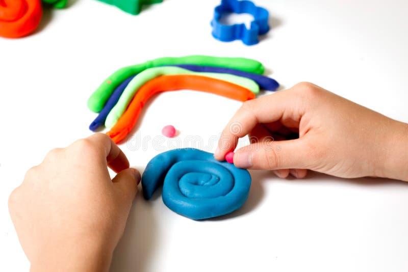 Kinderhandformteil Modellierton oder Plasticine auf wei?er Tabelle stockfotos