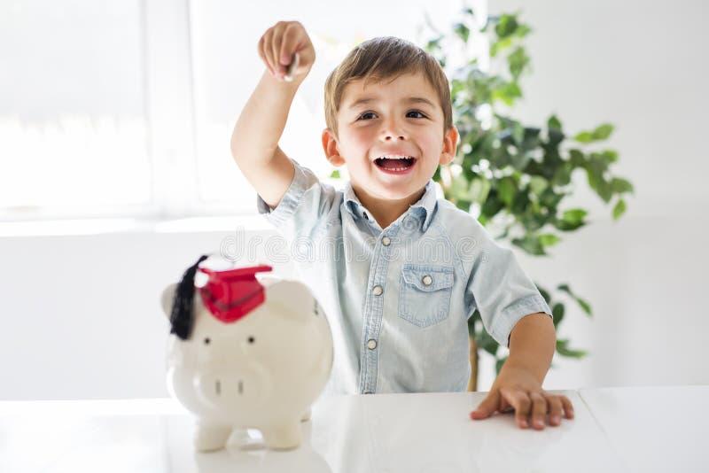 Kinderjaren, geld, investering en gelukkig mensenconcept die - weinig jongen met spaarvarken en geld thuis glimlachen stock foto