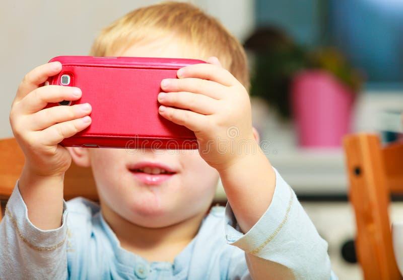 Kinderjaren. het kind van het jongensjonge geitje het spelen met mobiele telefoon stock afbeeldingen