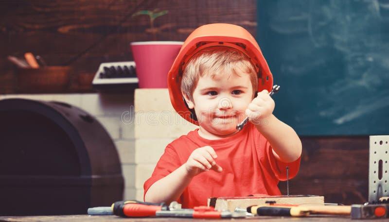 Kinderjarenconcept Kind die over toekomstige carri?re in architectuur of de bouw dromen Jong geitjejongen in oranje bouwvakker of stock afbeelding