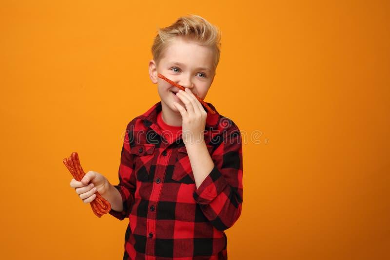 Kinderjongen eet droge worst stock afbeelding