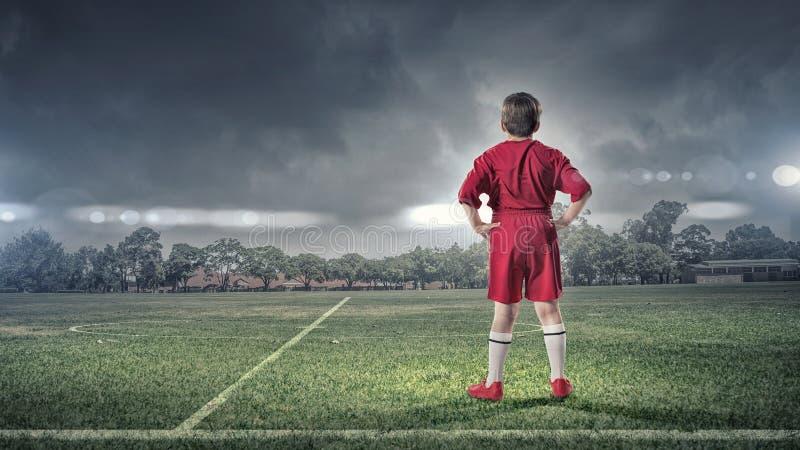 Kinderjunge auf Fußballplatz stockbild
