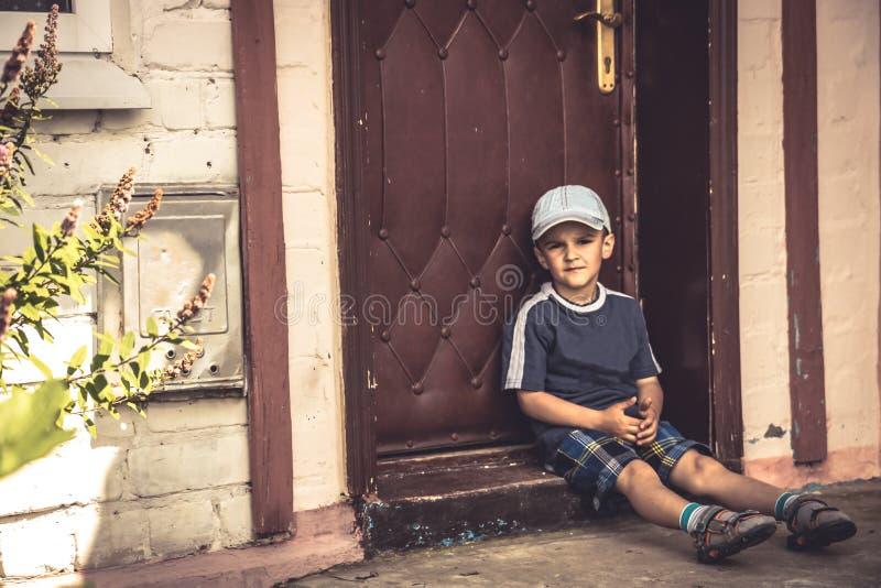 Kinderjunge bestrafte das traurige Bohrensitzen einsam auf Vortreppe stockfotografie