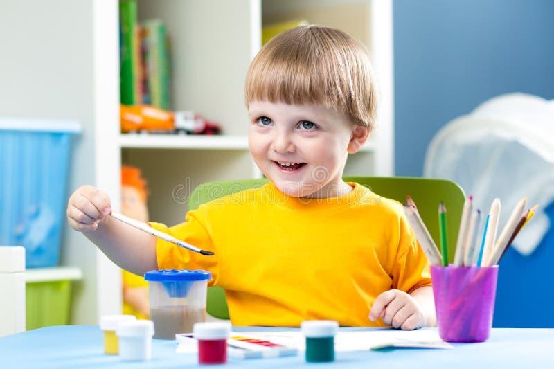 Kinderjunge, der bei Tisch im Kinderraum malt lizenzfreie stockfotos