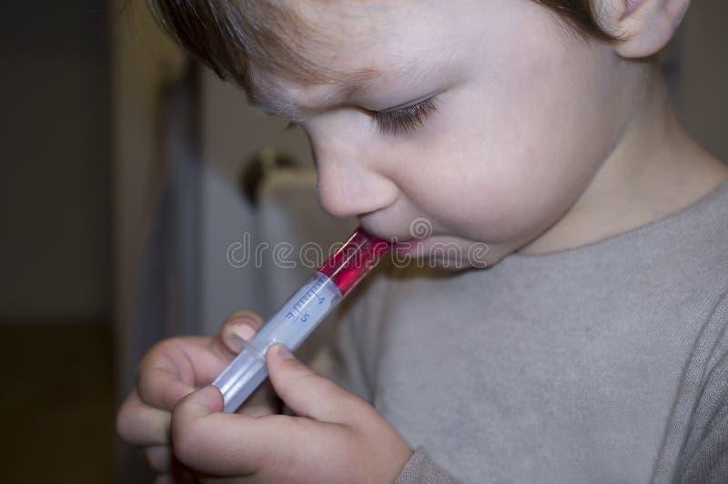 Kinderjunge, der fiebervermindernde Medizin mit messender Spritze hat lizenzfreie stockfotografie