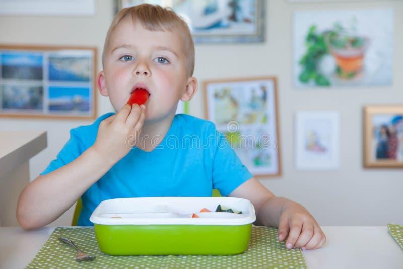 Kinderjunge, der Frischgemüsesalat isst lizenzfreie stockbilder