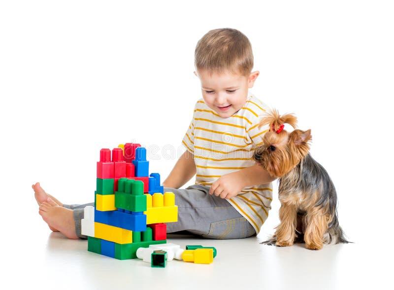 Kinderjunge, der mit Spielwaren und Hund spielt stockfoto