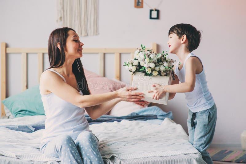 Kinderjunge, der morgens der Mutter für Muttertag Blumen gibt lizenzfreies stockfoto